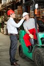 Supervisor instructing forklift driver at warehouse Royalty Free Stock Photography