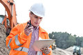 Supervisor reading clipboard while using walkie-talkie at construction site Royalty Free Stock Photo