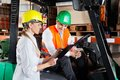 Supervisor showing clipboard to colleague sitting female in forklift at warehouse Stock Image