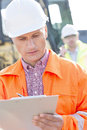 Supervisor writing on clipboard at construction site with colleague in background Stock Photo