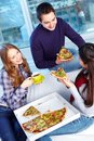 Supper image of teenage friends eating pizza together Stock Image
