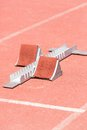 Support of foot athletics closeup starting blocks on red race track Stock Images