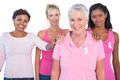 Supportive group of women wearing pink tops and breast cancer ribbons on white background Royalty Free Stock Image