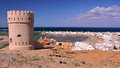 SUR, OMAN: General view of the beach of Ayjah with a watch tower in the foreground Royalty Free Stock Photo