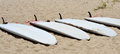 Surf boards several white lying on a beach Stock Photography