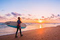 Surf girl with long hair go to surfing. Woman with surfboard on a beach at sunset or sunrise. Surfer and ocean Royalty Free Stock Photo