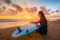 Surf girl and ocean. Beautiful young woman surfer girl with surfboard on a beach at sunset or sunrise. Royalty Free Stock Photo