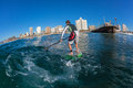 Surf rider sup catching wave durban a on his board standing photo image close up from behind unidentified male doing water Stock Image