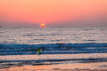 Surf ski athlete paddling out ocean sunrise male through the small waves with his craft as the sun rises for a dawn patrol Stock Photo