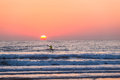 Surf ski athlete paddling sea sunrise horizon unidentified unrecognizable male out his fiberglass craft on the ocean waters as the Stock Image