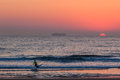 Surf ski canoe male entering ocean sun rising unidentified paddler the waters with his as the rises for a dawn patrol training Stock Image