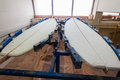 Surfboard blanks glueing wood stringers in half with glue in joining center in holding jig clamps at safari surfboards in durban Royalty Free Stock Photos