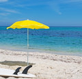 Surfboard and parasol white yellow beach umbrella on the sand Stock Photography