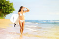 Surfboard woman walking in beach water holding bodyboard beautiful surfer girl white bikini going bodyboarding looking out over Stock Photos