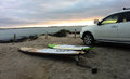 Surfboards next to suv at sunset paddleboards on the sand Stock Image