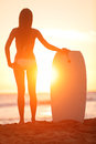 Surfer beach woman with water sport bodyboard surf girl enjoying sunset view and summer sunshine after bodyboarding on travel Stock Image