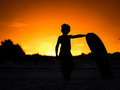 Surfer child a silhouette of a boy and his board on the beach at sunset Stock Photography