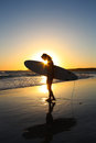 Surfer en at sundown a young female with a surfboard under her arm with in the background Stock Photos