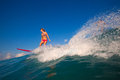 Surfer girl in a bikini ride the wave Stock Photography