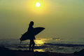 Surfer girl surfing looking at ocean beach sunset. Silhouette  w Royalty Free Stock Photo