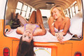 Surfer girls beach lifestyle beautiful relaxing in the back of classic vintage surf van on the at sunset Royalty Free Stock Photo