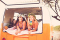 Surfer girls beach lifestyle beautiful relaxing in the back of classic vintage surf van on the at sunset Stock Images