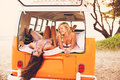Surfer girls beach lifestyle beautiful relaxing in the back of classic vintage surf van on the at sunset Royalty Free Stock Image