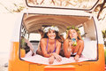 Surfer girls beach lifestyle beautiful relaxing in the back of classic vintage surf van on the at sunset Royalty Free Stock Photos