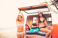 Surfer girls beach lifestyle beautiful relaxing in the back of classic vintage surf van on the at sunset Stock Image