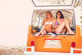 Surfer girls beach lifestyle friends hanging out eating watermelon in the back of classic vintage surf van on the at sunset Royalty Free Stock Images