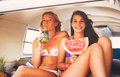 Surfer girls beach lifestyle friends hanging out eating watermelon in the back of classic vintage surf van on the at sunset Stock Images
