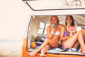 Surfer girls beach lifestyle friends hanging out eating watermelon in the back of classic vintage surf van on the at sunset Stock Photography