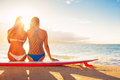 Surfer girls on the beach at sunset summer outdoor lifestyle best friends hanging out Stock Photo