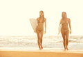Surfer girls beautiful walking on the beach at sunset Royalty Free Stock Photos