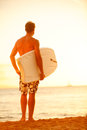 Surfer man on beach at sunset holding bodyboard surfing fit male body guy enjoying and bodyboarding summer Stock Photos