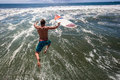 Surfer pier jump mid air ocean jumping with surfboard into off to surf waves at surf city durban south africa Stock Images