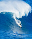 Surfer riding giant wave extreme ocean in hawaii Royalty Free Stock Photo