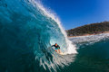 Surfer riding hollow wave water photo surfing rider with skill and courage inside a large standing upright a into a tube ride over Stock Images