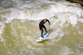 Surfer surfs at the isar in huge munich germany april waves for season opening event wittelsbacher bridge heart of Stock Image