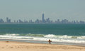 A surfer walking along the beach with the gold coast skyline in the distance Royalty Free Stock Image