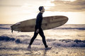 Surfer wals on the beach with board walking along ocean sportive man going to surf a tropical Stock Images