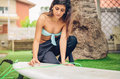 Surfer woman with bikini and wetsuit waxing closeup of beautiful her surfboard in front of palm tree summer sports concept Royalty Free Stock Photography