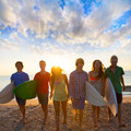 Surfers boys and girls group walking on beach teen at sunshine sunset backlight Stock Photos
