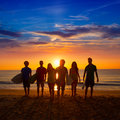 Surfers boys and girls group walking on beach teen at sunshine sunset backlight Royalty Free Stock Image