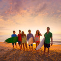 Surfers boys and girls group walking on beach teen at sunshine sunset backlight Royalty Free Stock Photography