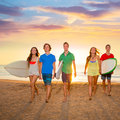 Surfers boys and girls group walking on beach teen at sunshine sunset backlight Royalty Free Stock Photos