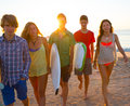 Surfers boys and girls group walking on beach teen at sunshine sunset backlight Royalty Free Stock Photo