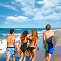 Surfers boys and girls walking rear view on beach teen group of Stock Photography