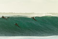 Surfers escape large wave cyclone paddle hard over summer from swells at surf city durban Stock Photo