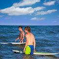 Surfers waiting for the waves on the beach boys blue Royalty Free Stock Photos